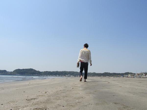 波打ち際を歩く男